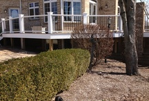 Trex Railing with Aluminum Spindles / This deck has over sized newel posts and with transcends railings with black metal spindles, brick columns, and picture framed steps.