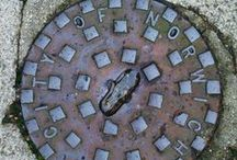 Manhole lids and covers / Photo collection of manhole lids and tap covers. The conception is that the photo has to be taken of a genuine local cover in its native environment that ideally displays the name of the settlement or shows something (e.g. a simbol, coat of arms) that is related to the place.