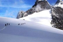 """Mountains of the Moon - Uganda / On the Congo / Uganda border are the legendary """"Mountains of the Moon"""", snow-capped and often shrouded in mist and clouds. Known locally as the Rwenzori Mountains they are considered one of the key `must climb' goals for alpinists around the world. To the south, one may also climb and camp on the caldera rim of Nyiragongo Volcano, the world's most active and largest permanent lava lake, and trek gorillas and chimpanzees on the lower slopes of the nearby Virunga Volcanoes."""