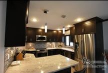 Modern Kitchen August 2015 / This photo gallery shows a Kitchen Remodel in which a wall was removed and the decor desired was modern. The Mosaic Backsplash, Light stone Countertops, and Dark Cabinets all flow perfectly together. Removing the wall allowed for more of a modern open floor plan while at the same time proving an island for eating, more counter space, and more cabinets for storage compared to the original kitchen design. Take a look at the gallery.
