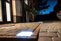 Świecąca kostka brukowa LED Qube / Świecąca kostka brukowa LED Qube™ to nowoczesne i oryginalne źródło światła powierzchni brukowanych. Dzięki zastosowanej technologii oraz starannie zaprojektowanym kształtom idealnie komponuje się z przestrzenią prywatną oraz publiczną. Znajduje zastosowanie w ciągach komunikacyjnych, takich jak chodniki, parkingi, drogi rowerowe, podjazdy, a ponadto służy do oświetlenia schodów, tarasów i wszelkich innych przestrzeni zewnętrznych.