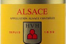 Wino - Francja - Alzacja / Położona przy granicy niemiecko francuskiej Alzacja, poprzez dzieje historii zawdzięcza swój charakter obydwu kulturom. Nie inaczej jest z winami. Produkując najczęściej odmianowe, aromatyczne wina białe, ukazuje wiele twarzy – od krystalicznych i orzeźwiających Rieslingów, przez krągłe i mineralne Pinot Gris i Pinot Blanc, po aromatyczne i zapadające bez trudu w pamięci Muscat i Gewurztraminer. Ciekawostką jest też lokalna wersja Pinot Noir.