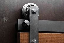 """Axel Barn Door Hardware / MODERN INTERPRETATION OF A CLASSIC Axel is our interpretation of the original flat track sliding barn door hardware design that has been in use for over a hundred years. Axel utilizes the same raw steel material and track construction as those original systems, but is redesigned to be quieter, safer, and more durable. Exposed 3"""" custom-engineered bearings and rugged visible fasteners create a product with a beautiful raw edge, and clean, modern aesthetic."""