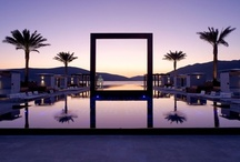 Lido Mar / An 80 metre infinity edged swimming pool builtover theAdriatic. The stunning vista from theshore along the length of the pool is accentuated by the addition of six mature palms on the pool's edge, and a large bronze square viewing frame, which rises seamlessly from thewater's surface to framethe view of theBalkansbeyond.