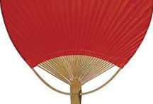 """Hand Fans - Paper Paddle / Our paper hand fans will keep you cool in summer, but also they're beautiful as decor in any season. They make great party decorations - use them with our matching-color parasols and lanterns for a very festive look. Our hope is that planning your party or wedding will be a little easier and a lot more fun! Bamboo frame. 9.5"""" wide by 14.5"""" long."""