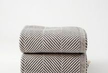 bedroom / soft cosy throws hung over armchair; plush pillows in a pile