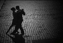 Sesja Tango / Sesja w klimatach tanecznych - tango. Kolorystyka biel, czerń i czerwień.  Tło - sala taneczna lub adekwatne miejsce publiczne. Stylizacja: ona - czerwona lub czarna sukienka, mocny makijaż, kręcone włosy; on - czanry strój (spodnia + koszula lub koszulka bez rękawów) + czerwone szelki.