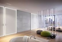 S1200 LED / W najnowszych drzwiach S1200 LED barwa i natężenie światła zmieniane jest dowolnie przez użytkownika.Zaprogramować je można także w sposób zgodny z biorytmem człowieka, co korzystnie wpływa na jego samopoczucie. Przykładowo, niebieskawa barwa pojawiająca się około południa wpływa pozytywnie na koncentrację. Natomiast żółte światło o zachodzie słońca spowalnia biorytm i pomaga odpocząć. Kolor i natężenie światła regulowane są pilotem lub przez aplikację na smartfona.