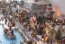 """Christmas Village 2015 / I have rearranged the village base this year and added some new pieces. It is 11 1/2 ft wide and 38"""" deep at its narrowest point and 54"""" deep at the widest point. I made two new pond/creeks with waterfalls that start from the top level of the village to the bottom of the village base. The two bases for each section of the creek/pond that hold the wildlife and water are made of styrofoam. The dock and the wooden bridge by the dock are made of Styrofoam, Popsicle sticks and twigs."""