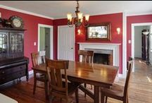 Home Decor: Library & Music Room / Benjamin Moore Confederate Red paint on walls . Lots of White Accents: White Mantel,  White Built-In Bookshelves, White Crown Molding, White Window Frames with 12 on 12 Colonial Grid Mullions . Tan leather couch . Red Floral Drapes ... very rich
