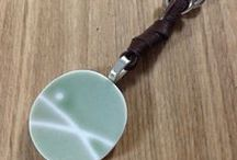 """Nagi  / Nagi is the name of the oldest daughter of one our staff, Yuko M.  As she grows up we hope she will find much love and hope! A female name meaning calm, this hand-knotted, soft leather necklace holds a one-of-a-kind pottery shard pendant.  Three silver rings above the pendant represent tears of joy and a ring of hope.  Cord ends are finished with a silver S-hook closure and accent beads. Chocolate or black leather. 18""""- 20""""L"""