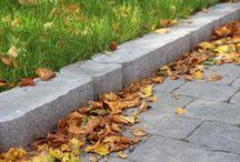 Nurmikonreunakivet / Curbstones / Kerbstones / Reunakivet tukevat kiveyksen reunaa ja pitävät kiveyksen kestävänä. Pihan hoito helpottuu, eikä nurmikon ja istutusalueiden reunoja tarvitse kantata siistin rajauksen aikaansaamiseksi. Reunakivillä saadaan tehtyä pieniä korkoeroja päällystealueille ja rajattua istutusalueita.