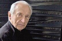 Pierre Soulages (1919- ) / Pierre Soulages, né le 24 décembre 1919 à Rodez dans l'Aveyron, est un peintre et graveur français associé depuis la fin des années 1940 à l'art abstrait. Il est particulièrement connu pour son usage des reflets de la couleur noire, qu'il appelle « noir-lumière » ou « outrenoir ». Ayant réalisé quelque 1 550 tableaux1 dont les titres sont tous composés du mot « peinture » suivi de la mention du format n 1, il est un des principaux représentants de la peinture informelle.