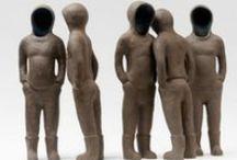 """Natasja Lefevre / Fragiele beelden in keramiek gemaakt door autodidact Natasja Lefevre. Haar beelden zijn gepuurd uit het innerlijke en fungeren als spiegels waarin we onszelf kunnen testen, zoeken naar een standpunt of er in confrontatie een tastbaar gesprek mee aangaan. Zo leren we misschien iets over de eigen innerlijkheid en kunnen we onszelf in onze werkelijkheid aanschouwen. Een bekend werk van haar is de installatie """"Hoop"""" gemaakt naar aanleiding van het Kunstenfestival Watou 2011."""