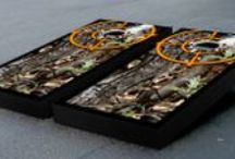 "Hunting & Camo Cornhole Themes / Our specialty cornhole games are made proudly in the USA. Each game set comes with two 24""x48"" regulation boards with folding legs, a complete bag set (8 bags), and a FREE string pack to carry the bags (A $10 value!)."