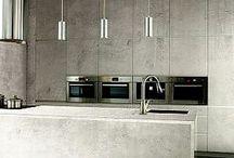 Habillage de cheminée / revêtement de mur et sol en pierre, acier et béton.