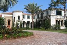 Colonial Mediterranean / Classic Palm Beach Mediterranean residence with stucco and stone detail capped with a terra cotta barrel tile roof.