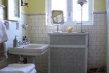 Bathroom decorating ideas / Our bathroom perks: (1) window in center of room (2) nice floor tile (3) good overhead lights above tub (4) high ceiling (5) great, old-style cast iron tub.  Bathroom negatives: (1) small size (2) cadilac of all toilets (3) ugly, bulky green counter (4) half rose/half mint green tile (5) 80's style box lighting (6) generally feels smaller than it could b/c of bulky cabinet, toilet and lighting. CHALLENGE-Make the b/r feel bigger, clean, adequate storage, use space well.