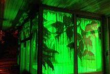 Jolanda Muilenburg / Voor het Festival Verboden Landschap © GANG heeft Jolanda Muilenburg de ramen van de Portiersloge beschilderd met uit de hand gelopen bladmotieven en een grillig patroon van druipers. In de avond licht het groen op tussen het verticale bos van druipers. 11 t/m 20 okt 2013.