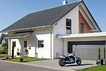 Garagen & Carports / Der Carport ist harmonisch in die Gesamtarchitektur integriert, die Garage hat die passende Dachform und die Pergola mit natürlicher Begrünung spendet der Terrasse im Sommer Schatten.  Wir planen und bauen alles, was Sie sich für Ihr SchwörerHaus wünschen bis hin zur Dachterrasse auf der Garage.