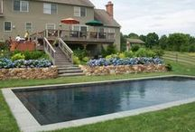 Natural Setting Pool Garden / When installing a pool, it is not necessary to adhere to the status quo. Why not have a pool with dark plaster instead of aqua blue? Try natural blue stone coping and grass in lieu of traditional pool decking materials.