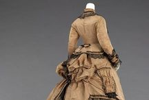 Bustles, Round One / First generation bustled gowns, circa approximately 1868-1875, had a shape that could be described as R-line-- that is, A-line skirts topped with a pouf. Waists were at the natural position, often belted; skirts were full and almost universally trained, at least a little; and sleeves were either lightly bell shaped, or in a relaxed fit with a large and elaborate cuff that recalled rococo sleeves. It was a heavily layered and ruffled aesthetic that was softer than the sleeker later bustles. / by calamity lulu