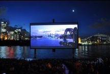 St. George Open Air Cinema  / St.George OpenAir Cinema is an extraordinary cinema and lifestyle experience that's staged each summer on Mrs Macquaries Point, Sydney. With stunning views over the Opera House, Harbour Bridge and city skyline, the centerpiece of the event is a massive screen that rises from the harbour at nightfall.