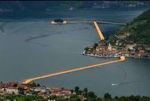 The Floating Piers - 18 Giugno 3 Luglio - Sulzano, lago d'Iseo / The Floating Piers, il nuovo progetto di Christo in Italia, reinterpreterà il Lago d'Iseo per 16 giorni dal 18 giugno al 3 luglio 2016. 70.000 metri quadri di tessuto giallo cangiante, sostenuti da un sistema modulare di pontili galleggianti formato da 200.000 cubi in polietilene ad alta densità, comporranno una installazione che si svilupperà a pelo d'acqua seguendo il movimento delle onde; l'opera avrà una lunghezza di 4,5 chilometri totali.