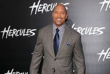 "Dwayne Johnson Style / Dwayne ""The Rock"" Johnson played football for the 1991 University of Miami national championship team. He took up professional wrestling like his father and grandfather and is still considered to be one of the greatest professional wrestlers of all-time. Since 2001 Johnson has starred in many television and film roles including Hercules (2014). Enjoy the Famous Outfits of Dwayne ""The Rock"" Johnson"