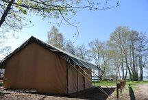Glamping @ Naturcamping Zwei Seen am Plauer See /  Safarizelte  Zelten kann Luxus sein: Wenn das Safarizelt bereits fertig aufgebaut und komplett möbliert ist (u.a. mit Boxspringbetten, voll ausgestatteter Kitchenette, Grill und LCD-TV) und einen fantastischen Blick von der großen überdachten Terrasse mit Loungemöbeln auf Sonnenuntergänge bietet. Die Stoffvilla direkt am Plauer See ist eine außergewöhnliche Mietunterkunft mit viel Platz & Komfort für 4-5 Personen, auch mit Hund.