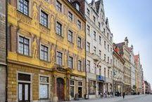 """LeoApart - Apartament 4 Pokoje / """"4 pokoje"""" to apartament tak zakręcony, jak film o tym samym tytule. Mieszkanie znajduje się w Kamienicy Pod Siedmioma Elektorami, budynku, który posiada jedną z bardziej zdobnych fasad na wrocławskim Rynku. Front kamienicy to istny przepych: gzymsy, płaskorzeźby, potężne figury elektorów i cesarza Leopolda, tyle, że to wszystko jest… iluzją!"""