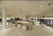 Interior design of a luxury women's clothing shop / The element that imparts both coherence and tranquillity to a seemingly lax arrangement of furniture, both free-standing pieces and wall units, is its geometrical features and a module discernible in its proportions, in the floor mosaic, and in the intervals of components placed in and on the suspended ceiling. The design is governed by a minimalistic approach characterized by great attention to details and economy of the form.