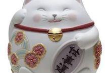 maneki neko . lucky cat´s / Maneki Neko (招き猫) je druh japonské sošky, často z keramiky, která má přinášet štěstí a bohatství svému majiteli.  Tradičně je zobrazena ve vzpřímené poloze se vztyčenou přední tlapkou.  Toto gesto ruky je v japonské kultuře chápáno jako gesto pozvání. Tvrdívá se, že když kočka zvedá pravou tlapku přitahuje peníze, když levou tlapku přitahuje zákazníky. Na krku má Maneki Neko vždy červený obojek s rolničkou.