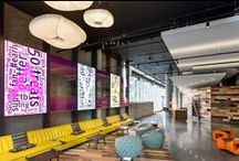"""AVA 55 Ninth   San Francisco, CA / New 17-story multi-family high-rise in San Francisco's Mid-Market neighborhood, adjacent to Twitter HQ. Fun design twists like the """"Twitter Wall"""", an interactive digital media hub of moving and ever-changing word clouds and the """"Ridiculously Long Sofa"""", which measures 30' long, complete with cup-holders and USB ports for plugging in while tuning up or out, were developed to capture the minds and moment of the tech-savvy residents."""