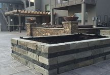 Luxury outdoor spa / Swim spa, sunken with raised seat walls. Fire bowls add to the ambiance, natural stone walls meld it into the natural surroundings..