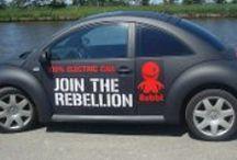 Rebbl / In het logo van Rebbl is de merkpersoonlijkheid – een jongetje van zeven jaar – tot leven is gekomen. Het beeldmerk wordt liefkozend 'The Stig' genoemd. De grijns op het gezicht symboliseert de 'EV Grin'. De glimlach ('grin') die je krijgt als je voor het eerst met een 'Electric Vehicle' rijdt. Onder het motto 'there is such a thing as a free ride' is het visitekaartje van Rebbl direct een voucher voor een gratis proefrit.  Huisstijl en thematiek ontwikkeld door Dizain (www.dizain.nl).