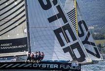 """Sponsor des Monocoques Psaros 40 / SYZ sponsorise deux monocoques de course sur le lac Léman. Ces voiliers, """"SYZ"""" et """"OYSTER Funds"""", sont des bateaux """"high tech"""" de 12.30m de long de type Psaros 40. Créés pour gagner, ces voiliers représentent à nos yeux la combinaison du meilleur de la tradition vélique avec la technologie la plus avancée. Ils cherchent la victoire sans solutions extrêmes, ni risques excessifs. C'est ainsi une parfaite illustration de ce que nous faisons chez SYZ."""