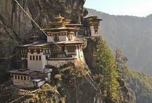 """""""Kuzu zangpo la"""" in Bhutan / Bhutan – das Land des Donnerdrachens. Auf der Erde gibt es wohl kaum ein einzigartigeres Reiseziel – selbst für passionierte Weltreisende ist dieses Land ein Privileg. Sicherlich zählt das Wandern im kleinen Königreich zu den schönsten Unternehmungen…. Aber auch kulturell hat Bhutan mit alten Klöstern und buddhistischer Architektur einiges zu bieten! Nicht zuletzt finden Naturliebhaber unterberührte Landschaften am Fuße des Himalaya Gebirges."""