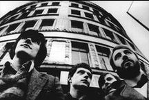 Joy Division / An English post-punk band formed in 1976. The band consisted of Ian Curtis b. 1956, d. 1980 (vocals), Bernard Sumner b. 1956, (guitar and keyboards), Peter Hook b. 1956 (bass) and Stephen Morris b. 1957 (drums). Ian Curtis died in May 1980. The remaining members then formed New Order.