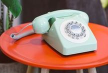 """Retro Phones / Not until the 1920s did the telephone companies catch on to what people really wanted from this wonderful machine. They wanted to be drawn into a kind of living tether with one another. The Bell Company started telling long-distance customers, """"Your voice is you!"""" In the 30s, AT&T first suggested that we """"Reach out and touch someone."""" And today, even in business, that's how we use telephones. Telephones unite our scattered families and keep friendships alive."""