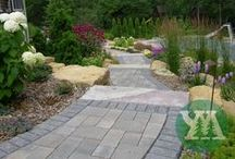 Walks and Entryways / Improve your curb appeal, accentuate your home, and define your landscape with a custom designed walkway or entryway by Yardmasters Landscapes. Walkways and entryways not only beautify your landscape, but direct foot traffic, and prevent damage to lawns and plantings. With a variety of materials to choose from such as natural stone, pavers, or decorative concrete, we can give your landscape a distinctive visual touch.