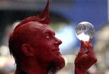 He Who Is Red / He Who Is Red is a calm, confident and cheerful character, replete with the mischievous edge one might expect of a man painted red. His magical and mesmeric manipulation of a crystal ball completes the experience and has to be seen to be believed!