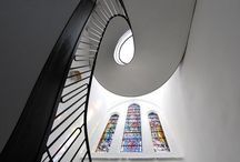 Helical Staircases / This beautifully sculptured double flight helical staircase, designed and manufactured by Elite Metalcraft, has the hallmark of dedicated craftsmanship in metalwork and innovative design.  It enhances the visual harmony of the stained glass windows with the hand crafted metalwork. Ground to first floor 4100mm, First to second floor 2950mm balustrade was laser cut steel and polished prior to chemical patination process.  All exposed steel in Gun Metal finish.
