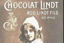 VINTAGE LINDT / A board filled with vintage chocolate advertising for Lindt and Lindor.