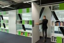 Team V // Fonds 21 / Characteristic of the office interior are the two white shelving units with a random pattern of bright green translucent cabinet doors. The shelves are fitted seamlessly around the existing structure of V-shaped columns, which divides the office visually in three areas. By taking the dominant column structure as a basis for the design, it becomes a natural part of the interior and the spaciousness of the workplace is optimally used. Photography ©Katja Effting