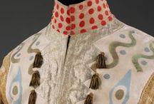 Veste / Dress / Basta poco e cambiamo: Un pezzo di tessuto, una gallina imbalsamata in testa, un mantello ricamato, una busta di plastica, una corona... E' tutto un gioco: il gioco che ci porta verso la purezza dello spirito che ci fa rinascere