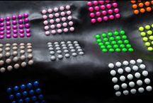 Le nostre creazioni - Our creations / Strass, pietre, borchie, perle e occhielli vestono il tessuto e la pelle creando motivi geometrici, paesaggi fantastici e trame luccicanti