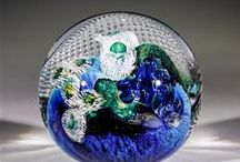 Glass Planet Paperweights / Hand made solid glass paperweights by American glass artist, Josh Simpson.  Josh Simpson has created a paperweight that is packed with visual information. The result is a work of astonishing depth and intricate beauty. Each of these paperweights is handmade, so no two are exactly alike in color or shape. These are around three inches in diameter, signed and dated by Simpson.