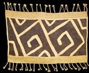 """African Textiles - Raffia Cloth / The Kuba people in D.R. Congo are known for their unique textiles. Raffia fibers are peeled from the leaves of the raffia palm and most often dyed with natural pigments. These long """"skirts"""" are made of long lengths of the raffia fabric adorned with applique, piece-work, embroidery, and/or shells. Some of the pieces are constructed into cushion covers in a variety of styles."""