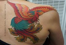 Inkspiration - Phoenix / Part of left arm sleeve. Colourful phoenix with wings spread out along collarbone upper arm with tail trailing down arm. Script and flowers tying into forearm